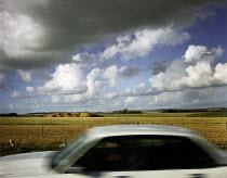 Car driving through the countryside, under a cloudy sky. - Paul Carter - 17-03-1995