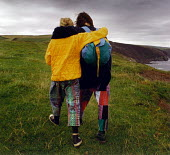 Two teenage girls seen from behind, walking along the North Cornwall coastal path. Near Crackington Haven. - Paul Carter - 1990s,1993,adolescence,adolescent,adolescents,affection,affectionate,bright,cliff,clifftop,clothes,coast,coastal,coastline,coastlines,coasts,country,countryside,destination,EMBRACE,EMBRACING,ENI envir