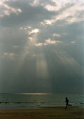 Man jogging along a sandy beach. Sun rays shining through the grey clouds creating a pool of light on the sea, Cornwall - Paul Carter - 01-08-1995