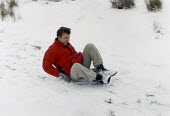 Young man sliding down a snow slope on a make shift sledge - Paul Carter - 2000,2000s,cold,EMOTION,EMOTIONAL,EMOTIONS,ENJOYING,enjoyment,fun,funny,HAPPINESS,happy,having fun,hill,Humor,HUMOROUS,HUMOUR,joking,laugh,laughing,laughter,LFL lifestyle & leisure,male,PLAY,playing,p