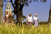 Two women enjoying a summer walk through the grounds of Royal Victoria Country Park, with the red brick chapel in the background. - Paul Carter - 20-07-1996