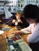 Two pupils during an technology lesson. One is using a soldering iron. - Paul Carter - 1980s,1988,adolescence,adolescent,adolescents,CDT,child,CHILDHOOD,children,class,classroom,CLASSROOMS,EDU Education,ELECTRONIC,electronics,female,females,girl,GIRLS,juvenile,juveniles,kid,kids,Laborat