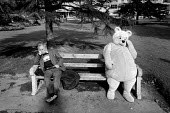 Man and bear relaxing on a park bench. - Paul Carter - 1980s,1987,ACE arts culture entertainment,bench,character,costume,depression,dressed up,dressing up,fancy dress,funny,Humor,HUMOROUS,humour,JOKE,JOKES,joking,LFL lifestyle & leisure,male,outfit,Pooh,r