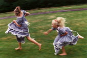 Two teenage girls playing chase. - Paul Carter - 1980s,1989,adolescence,adolescent,adolescents,bridesmaid,bridesmaids,catch,chasing,dress,dresses,EMOTION,EMOTIONAL,EMOTIONS,enjoy,ENJOYING,enjoyment,families,family,female,females,fun,funny,game,girl,
