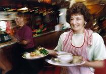 Woman serving food in a pub. - Paul Carter - 05-09-1993