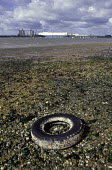 An old car tyre littering the beach. In the background there is a docked ship. - Paul Carter - 01-04-1991
