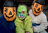 Children wearing plastic Halloween Masks. - Paul Carter - 1990s,1999,ACE,ACE arts culture & entertainment,CELEBRATE,CELEBRATING,celebration,CELEBRATIONS,child,CHILDHOOD,Children,costume,Culture,dressing up,enjoying,enjoyment,evil,face,FACES,festival,FESTIVAL