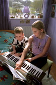 Two children practicing playing their electronic keyboard after school. - Paul Carter - 04-04-2002