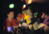 Young woman in a nightclub talking on a mobile phone - using a hands free kit - Paul Carter - 10-02-2000