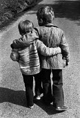 Two boys walking with their arms round each other. - Paul Carter - 1970s,1978,BOY,boys,brother,child,CHILDHOOD,children,EMBRACE,EMBRACING,families,family,friend,friends,friendship,friendships,hug,hugging,hugs,juvenile,juveniles,kid,kids,male,people,relax,relaxing,str