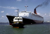 The Cunard cruise liner QE2 being towed from Southampton docks. - Paul Carter - 1980s,1989,2nd,boat,boats,cruise,dock,EBF economy,elizabeth,holiday,HOLIDAYS,LFL lifestyle & leisure,liner,luxury,marine,maritime,maritime industry,merchant navy,nautical,port,ports,queen,sailing,seco