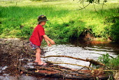 A young boy playing by a stream, the New Forest, Hampshire. - Paul Carter - 01-06-2002