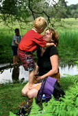 A mother helps her son put his socks on after paddling in a stream, The New Forest, Hampshire - Paul Carter - 01-06-2002