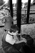 Two young boys on a trip to a zoo. They are looking through glass at an animal. - Paul Carter - 13-09-2001