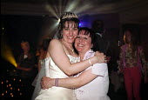Daughter hugging her mother during her wedding celebrations. - Paul Carter - 2000s,2002,adult,adults,bride,brides,celebrate,CELEBRATING,celebration,CELEBRATIONS,cuddle,Daughter,DAUGHTERS,disco,dress,EMBRACE,EMBRACING,EMOTION,EMOTIONAL,EMOTIONS,enjoying,enjoyment,event,families