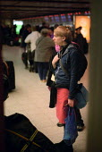 Young woman waiting near the check in desks at an airport. - Paul Carter - 01-04-2000