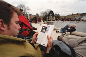 Young man reading a guidebook next to a boating pond in a park. - Paul Carter - 09-03-2000