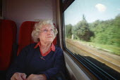 Elderly woman sitting in a train carriage, looking out of the window as the countryside speeds past. - Paul Carter - 15-09-2001