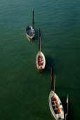 Small sailing boats tied to mooring posts on green water. - Paul Carter - 04-09-2003
