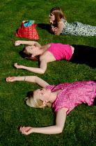 Three young women lying on the grass, sunbathing. - Paul Carter - 12-07-2003