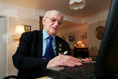 Elderly man using his laptop computer at home. - Paul Carter - 18-12-2003