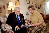 Elderly couple completing a newspaper crossword at home - Paul Carter - 18-12-2003