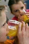 Children drinking glasses of orange juice. - Paul Carter - 2000s,2006,boy,boys,brother,child,CHILDHOOD,children,diet,dietary,diets,drink,drinking,families,family,fruit,FRUITS,glass,glasses,healthy,inside,Interior,juice,juvenile,juveniles,kid,kids,kitchen,KITC