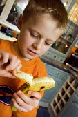 Boy peeling a banana. - Paul Carter - 2000s,2006,banana,bananas,boy,boys,child,CHILDHOOD,children,diet,dietary,diets,eat,eating,food,FOODS,fresh,fruit,FRUITS,healthy,home,inside,Interior,juvenile,juveniles,kid,kids,kitchen,KITCHENS,LFL Li