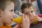 Children drinking glasses of orange juice. - Paul Carter - 2000s,2006,boy,boys,brother,child,CHILDHOOD,children,diet,dietary,diets,drink,drinking,families,family,female,females,fruit,FRUITS,girl,girls,glass,glasses,healthy,inside,Interior,juice,juvenile,juven