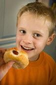 Young boy eating a doughnut. - Paul Carter - 07-01-2006