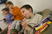 Children eating unhealthy snacks sitting on a sofa. - Paul Carter - 2000s,2006,bite,biting,boy,boys,brother,brothers,child,CHILDHOOD,children,chocolate,chocolates,crisps,diet,dietary,diets,eat,eating,families,family,fat,fatty,female,females,food,FOODS,girl,GIRLS,home,