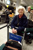 Elderly woman waiting in a queue at an airport check-in desk. She is pushing a trolley full of her luggage. - Paul Carter - 15-10-2003