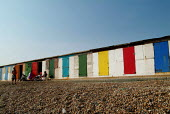 Family sitting out on a shingle beach, in front of row of brightly coloured doors of sea huts. Milford-on-Sea, Hampshire. - Paul Carter - 29-05-2003