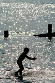 Silhouette of a young boy playing in the sea at Milford-on-Sea, Hampshire. - Paul Carter - 2000s,2003,boy,boys,calm,child,CHILDHOOD,children,COAST,coastal,coasts,eni environmental issue,holiday,holiday maker,holiday makers,holidaymaker,holidaymakers,holidays,juvenile,juveniles,kid,kids,LFL