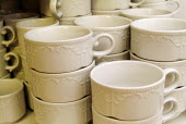 White china cups stacked in a cafe, waiting to be used. - Paul Carter - 2000s,2004,cafe,cafes,catering,ceramic,ceramics,china,crockery,cup,cups,ebf economy,patterned,wait,waiting,waits,White