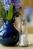 A brightly coloured jug of flowers on a cafe table, next to a salt and pepper pot. - Paul Carter - 27-07-2004