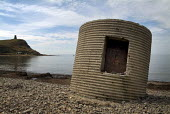 Concrete pillbox on the beach at Kimmeridge, Dorset with Clavel's Folly, or Kimmeridge Tower in the distance. - Paul Carter - 03-08-2004