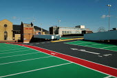 Brightly coloured tarmac of a the upper deck of an empty multi storey car park. Showing parking bays and pedestrian walkways. - Paul Carter - 24-09-2004