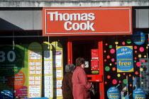 Two elderly women walk past a travel agent shop. - Paul Carter - 16-02-2000