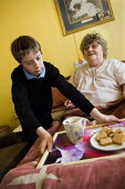 Young boy in school uniform, brings a tray of tea and biscuits to his bedbound grandmother.Young carers looking after elderly relatives. Photo posed by models. Model released. - Paul Carter - 14-11-2006