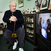 Elderly man with walking stick watches television in his lounge. - Paul Carter - 14-11-2006