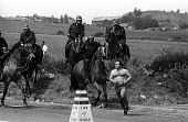 Riot police on horseback chase lone, bare-chested, striking miner at the Battle of Orgreave - a violent confrontation between police and picketing miners at the coking plant in South Yorkshire. The pi... - John Harris - 1980s,1984,adult,adults,animal,animals,Battle of Orgreave,CLJ,confront,confrontation,confronted,confronting,DISPUTE,DISPUTES,domesticated ungulate,domesticated ungulates,equestrian,equine,horse,horseb