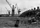 Derelict housing and the Swan Hunter Shipyard, Tyneside, Newcastle on Tyne - John Sturrock - ,1980s,1981,building,buildings,capitalism,capitalist,carrier,carriers,child,CHILDHOOD,CHILDREN,cities,city,cityscape,cityscapes,crane,cranes,deindustrialisation,Deindustrialization,DEMOLISH,DEMOLISHED