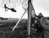 Women remove the fencing, at Greenham Common. - John Sturrock - 1980s,1983,activist,activists,against,Air force,air forces,Airbase,airbases,aircraft,aircrafts,airforce,anti war,anti-nuclear,Antiwar,armed forces,Barbed Wire,CAMPAIGN,campaign for nuclear disarmament