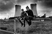 Unemployed youths sitting in front of a demolished factory. Behind are the cooling towers of ICI Billingham, Stockton-on-Tees 1980 - John Sturrock - 1980,1980s,adolescence,adolescent,adolescents,bored,boredom,boring,capitalism,capitalist,Chemical,Chemical works,CHEMICALS,close,CLOSED,closing,closure,closures,cooling,deindustrialisation,Deindustria