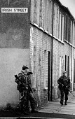 British army patrol in a Catholic area, Northern Ireland, 1985 - John Sturrock - 1980s,1985,armed,army,catholic,cities,city,gun,guns,Ireland,Irish,male,man,men,Northern Ireland,patrol,patrolling,patrols,people,person,persons,scene,scenes,soldier,soldiers,street,streets,The Trouble