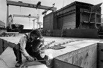 Harland and Wolff shipyard worker with welding equipment, Belfast, Northern Ireland, 1986 - John Sturrock - 1980s,1986,Arc,BUILDING,BUILDINGS,cities,city,construction,dockyard,dockyards,engineer,engineers,equipment,helmet,helmets,Ireland,Irish,LAB LBR Work,male,man,men,metal,metals,nautical,Northern Ireland