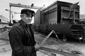 Harland and Wolff shipyard worker with welding equipment, Belfast, Northern Ireland, 1986 - John Sturrock - 1980s,1986,age,aged,ageing population,BUILDING,BUILDINGS,cities,city,construction,dockyard,dockyards,elderly,engineer,engineers,equipment,Ireland,Irish,LAB LBR Work,male,man,men,metal,metals,nautical,