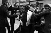 The arrest of a black youth, in Coldharbour Lane, at the start of Sunday afternoon Riot. - John Sturrock - ,1980s,1981,adult,adults,arrest,arrested,arresting,BAME,BAMEs,Black,BME,BME Black minority ethnic,bmes,cities,city,civil,CLJ,disorder,disturbance,diversity,ethnic,ethnicity,force,hold,holding,inner-ci
