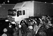 News International Dispute. Police and mass picket, Wapping, 1986. A TNT lorry breaking the strike. - John Sturrock - , News International,1980s,1986,adult,adults,CLJ,de recognition,derecognition,dismissed,dispute,DISPUTES,force,HAULAGE,HAULIER,HAULIERS,HGV,hgvs,INDUSTRIAL DISPUTE,LGV,LGVs,LORRIES,lorry,lorry lorries